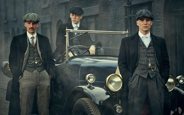 Drie Peaky Blinders die hun zakhorloge duidelijk zichtbaar dragen in hun waistcoat.